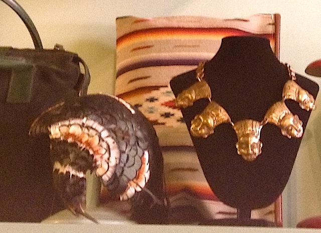 золотое колье и шляпка из перьев