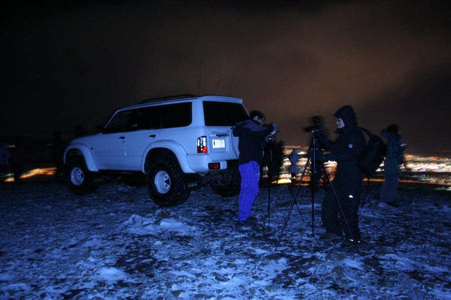 джип для путешествия по снежным горам и люди с фотокамерами