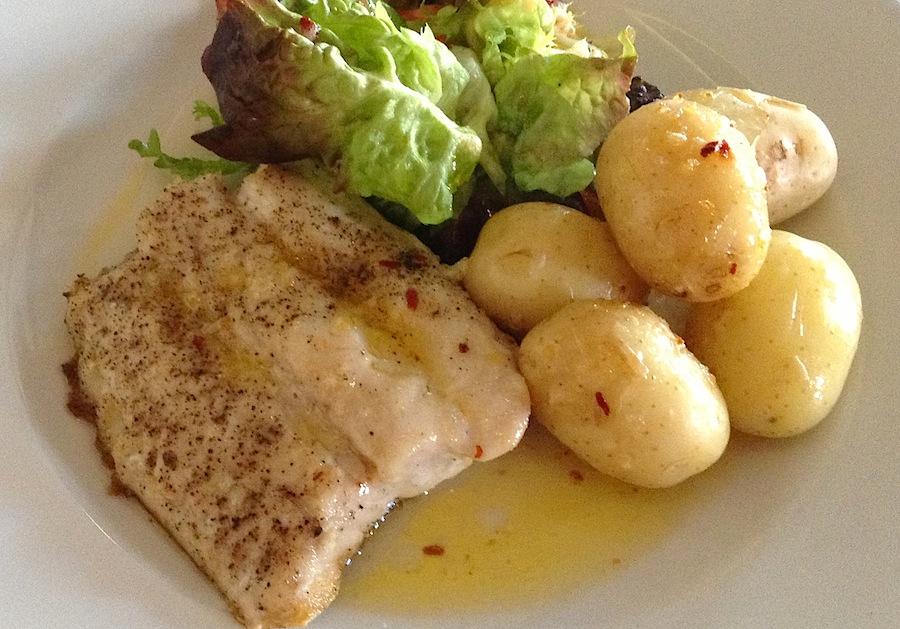 треска с картофелем и листьями салата, все приготовлено на сливочном масле
