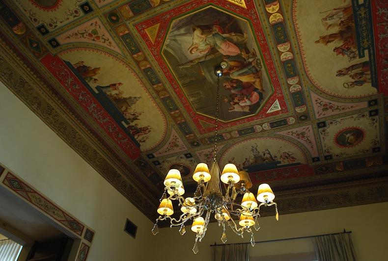потолок с фресками и люстра в Relais Santa Croce