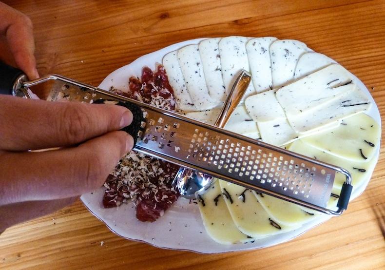 Колбасу и сыр посыпают стружкой из трюфеля
