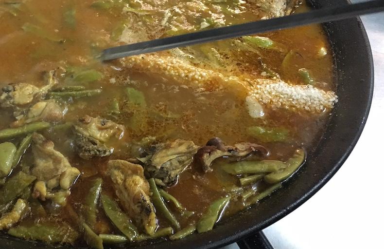 Осторожно, круговыми движениями с помощью шумовки распределите рис по сковороде. Помните, что после этого перемешать паэлью будет уже нельзя. Увеличьте огонь под сковородой и дайте получившемуся «вареву» немного покипеть.
