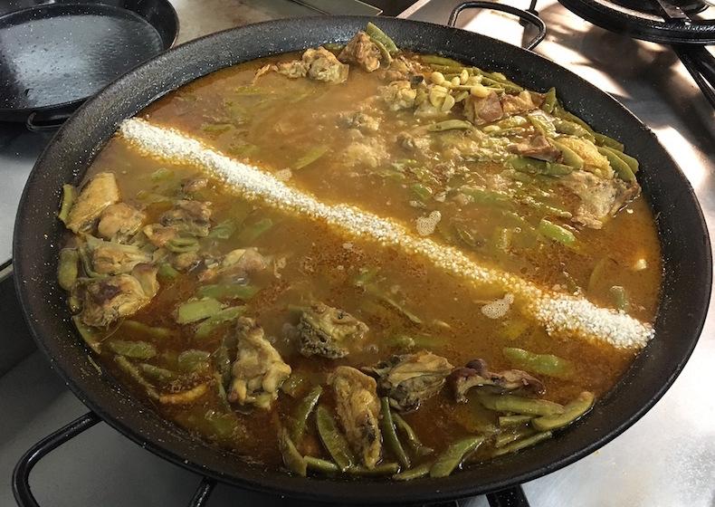 Выньте розмарин из бульона и посолите его по вкусу (на большую классическую сковороду для паэльи требуется 6 щепоток соли).