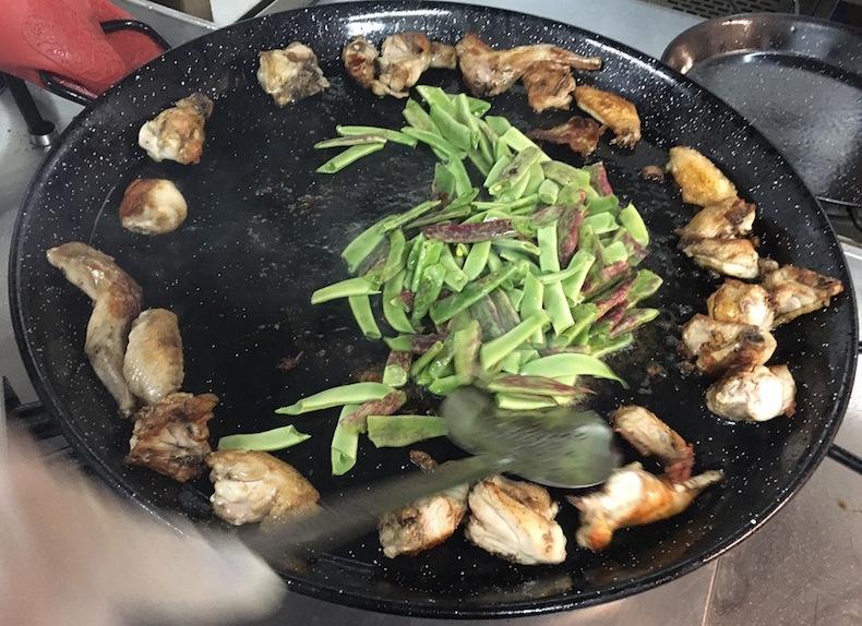Отодвиньте обжаренное мясо от центра и в образовавшийся круг выложите зеленую фасоль и обжарьте ее.