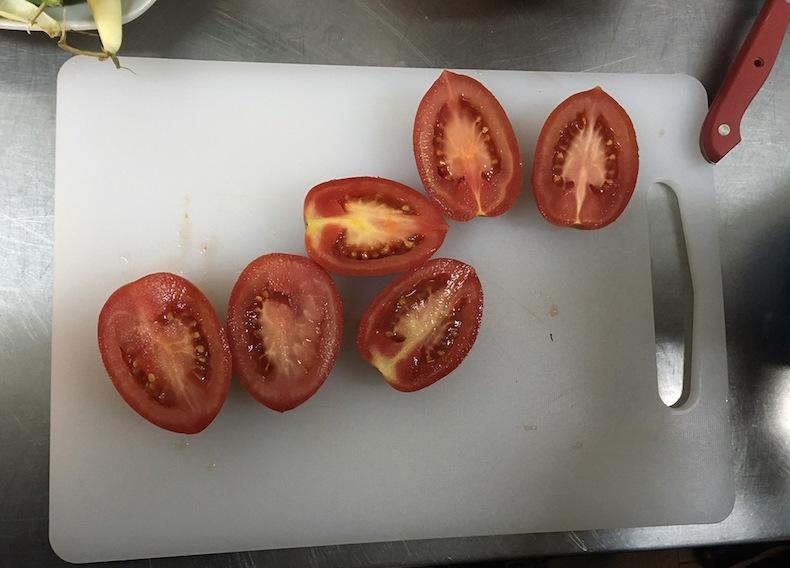 Пока бобы обжариваются, подготовьте помидоры: разрежьте их на половинки и натрите мякоть на крупной терке. Важный момент - кожура помидоров в паэлью не добавляется.