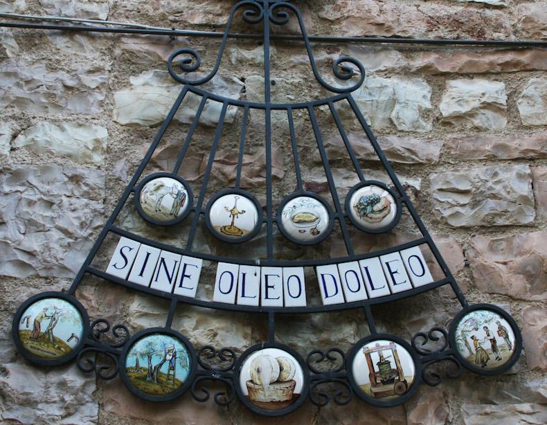 Надпись на латыни гласит: «Без оливкового масла я страдаю»