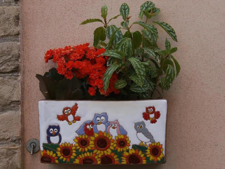 Кто-то сочетает приятное с полезным. Один магазинчик украсил стену цветами в ярких керамических горшках собственного производства